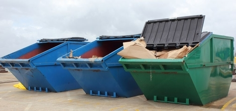 3 large enclosed skips 2 blue and one green) with lids open in skip hire yard