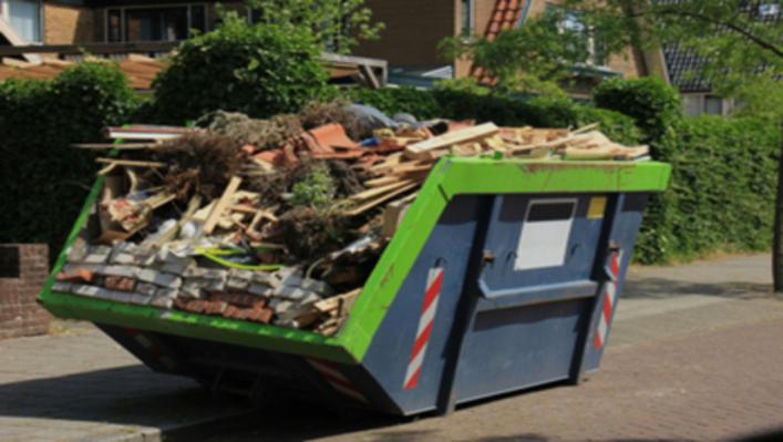 Large domestic skip on roadside full of wood, rubble and houshold waste