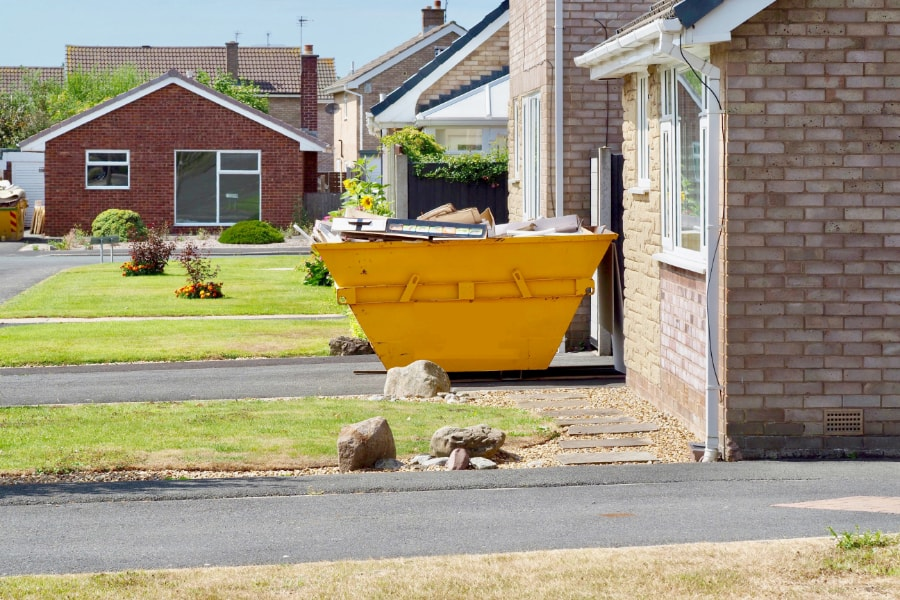 Small yellow mini skip full of household waste on driveway in Swansea