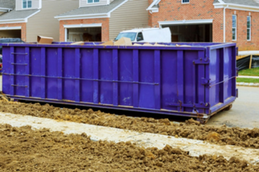 Large blue Ro-Ro Roll On- Roll Off Skip full of construction waste and cardboard boxes on construction site