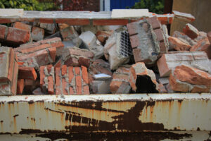 Close up shot of skip full of old house bricks and cement from dismantling of wall on a construction site