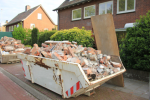 red and white maxi skip full of old cemnted house bricks after dismantling of wall in house renovation in Swansea. Also large wooden board leaning against skip