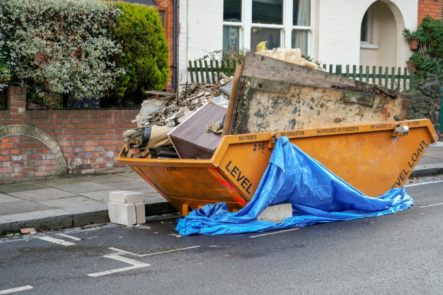 yellow maxi skip full of wood boards household rubbish also has blue taupaulin hanging off one side of skip