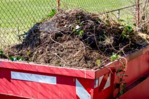 Read skip full to brim with garden waste, earth weeds and shrubs with mesh fencing in background