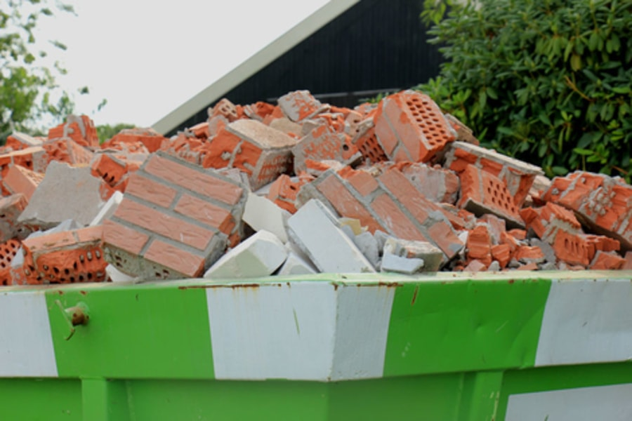 Large Green and White Builders skip full of old house bricks from demolition of wall